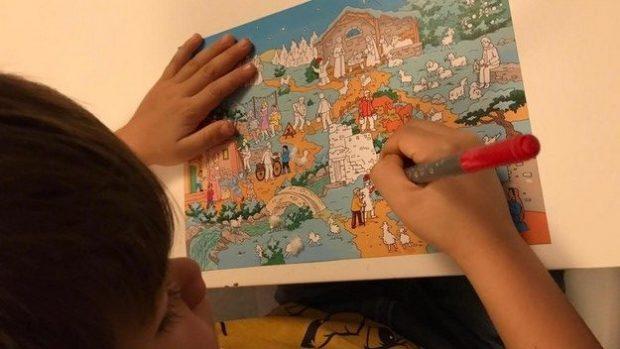 Un enfant colorie son calendrier de l'Avent